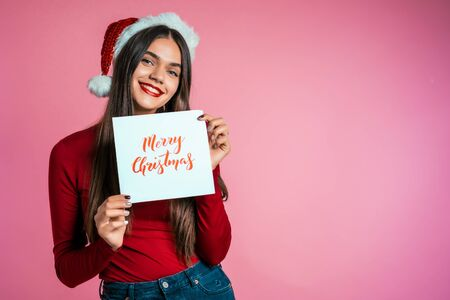Attractive girl in Santa hat with nameplate Merry Christmas. Portrait of lady on pink background. New year concept. Happy pretty woman smiling to camera.