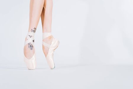Close up of ballet dancers legs in pointe. Woman practices exercises on white studio background. Ballerinas feet in shoes. Girl shows classic ballet pas 写真素材