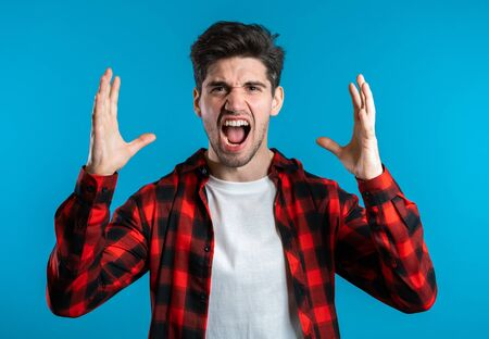 Young european stressed man in red shirt shouting isolated over blue background. Stressed and depressed guy loudly screaming to camera.