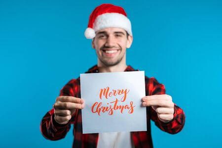 Attractive man in Santa hat with nameplate Merry Christmas. Portrait of guy on blue background. New year concept. Happy boy smiling to camera.