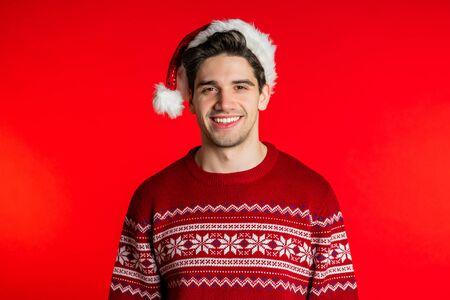 Portret van gelukkige jonge man in kerstmuts en kerst trui geïsoleerd op rode studio achtergrond. Wintervakantie concept. Stockfoto
