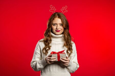 Young pretty woman smiling and holding gift box on red studio background. Girl with beautiful hairstyle in white sweater and deer horns. Christmas mood. Zdjęcie Seryjne