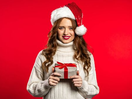 Young pretty woman smiling and holding gift box on red studio background. Girl with beautiful hairstyle in white sweater and Santa hat. Christmas mood.