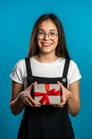 Young cute girl smiling and holding gift box on blue studio background. Cute portrait of female student. Christmas mood. Zdjęcie Seryjne