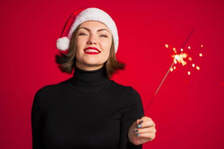 Trendy hipster girl in Santa hat with bengal sparkler fire on red background. Smiling, happy lady. Portrait of young pretty woman celebrating Christmas or New year party.