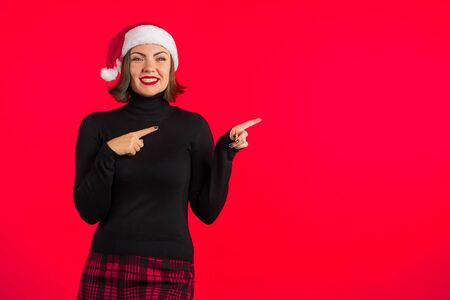 Copy space. Trendy hipster girl in black hat and plaid mini skirt showing to her left side. Smiling lady. Portrait of young pretty woman on red background in studio.