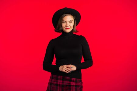 Portrait of young pretty woman on red background in studio. Trendy hipster girl in black hat and plaid mini skirt. Smiling lady.