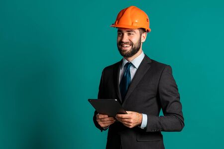 Young engineer businessman in suit jacket holding tablet with building project. Businessman isolated on blue background as on construction. Technology, modern occupation concept.