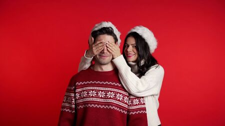 Woman closes eyes of her beloved boyfriend before surprise him. Couple in Santa hat on red studio background. Love, holiday, happiness concept.