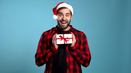 Young handsome man smiling and holding gift box on blue studio background. Guy in Santa hat. New year mood