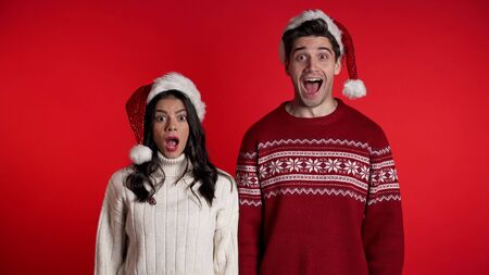 Amazed european man and woman shocked, saying WOW. Young couple in Santa hats surprised to camera over red background. Zdjęcie Seryjne