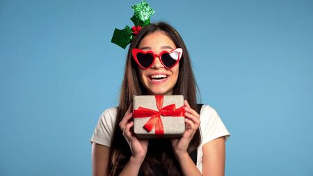 Pretty young girl smiling and holding gift box on blue studio background. Cute portrait in Santa hat. Christmas mood.