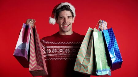 Handsome young man in Christmas sweater and Santa hat holds shopping paper bags on red studio background. Guy bought presents on sales with discounts.