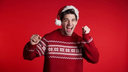Handsome european man in Santa hat and ugly sweater smiling and dancing in excellent mood on red background. Christmas, new year eve, party concept.