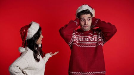 Young woman in Christmas hats emotionally screaming at her husband or boyfriend on red background in studio. Bored man covers ears with hands. Concept of conflict, problems in relationships. Stock Photo