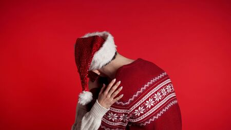 Portrait of young couple in Christmas Santa hats kissing and hugging on red studio background. Love, holidays, happiness concept. Zdjęcie Seryjne