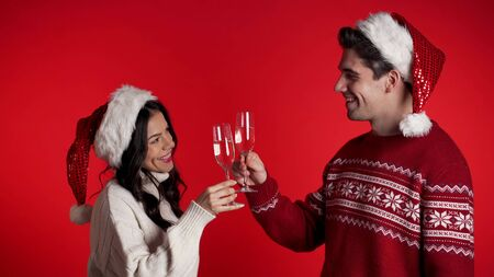 Portrait of young couple in Christmas Santa hats drinking champagne on red studio background. Love, holidays, happiness concept.