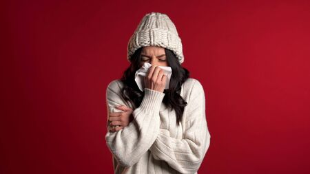 Young girl in warm knitted wear sneezes into tissue. Isolated woman is sick