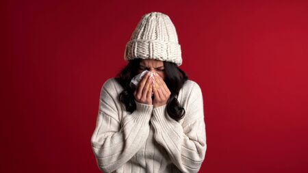 Young girl in warm knitted wear sneezes into tissue. Isolated woman is sick, has a cold or allergic reaction. Health, medicine, illness, treatment concept.