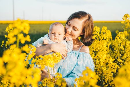 Young mother holding baby boy. Son having fun, smiling in yellow canola field. Love, family, joy concept