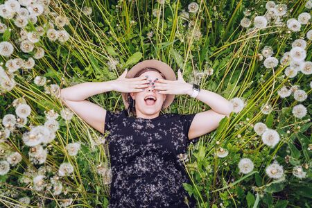 Young beautiful girl in sunglasses lies in dandelion field and shut her eyes with delight. Top view.