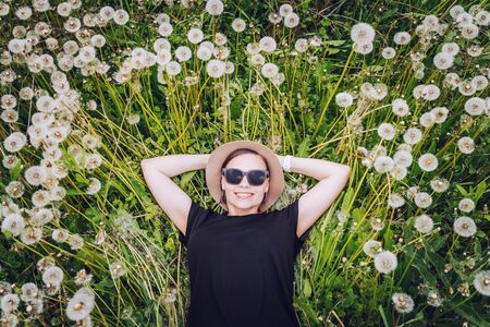 Young beautiful girl in sunglasses lies in dandelion field and looks to the sky. Top view.