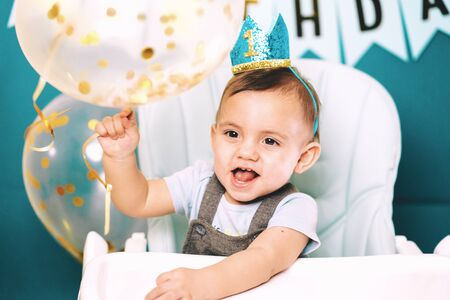 Cute baby boy sitting in his chair and playing with air balloon. Birthday handsome toddler child with big eyes portrait. Funny kid.