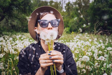 Happy woman blowing on dandelion in park. Girl in hat and sunglasses. Wishing, joy concept Zdjęcie Seryjne