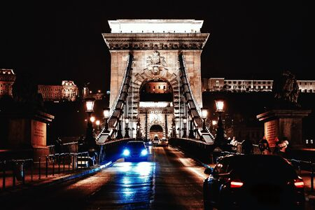 View to Chain bridge and city traffic. Beautiful evening or night scene of illuminating ancient architecture.