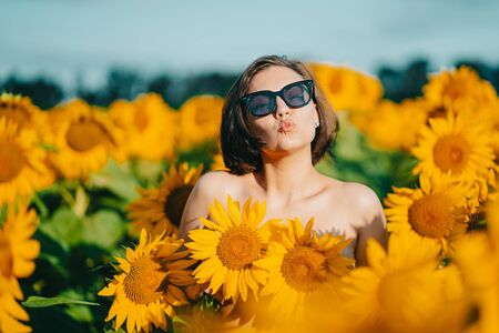 Funny portrait of nude woman with sunflowers on her chest. Cheerful cute kissing girl having fun. Summer concept.
