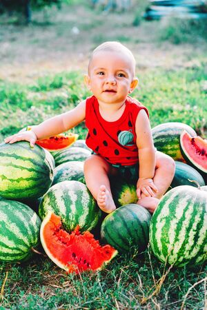 Happy little baby boy sitting on watermelons field or garden. Happy Infant child smiling, looking to camera. Kid on fruits outdoors. Healthy lifestyle concept.