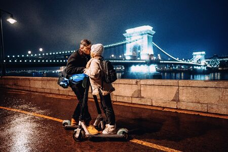 Young happy couple kissing with electric scooter outside in front of ancient european bridge in winter.