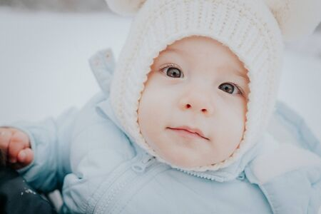 Cute portrait of little baby in winter hat with fluffy ears on snowy street background. family, son, toddler child concept. Zdjęcie Seryjne