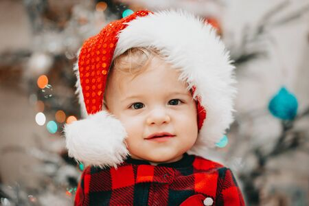 Very cute portrait of little baby boy in Santa hat on Christmas tree lights background bokeh. new year, family, son, toddler child concept.