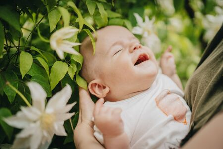 Beautiful portrait of little baby boy on flowers bush background. Child in spring blossom. Cute newborn son smiling
