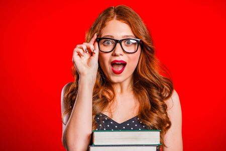Surprised excited female student on red background in studio holds stack of university books from library. Woman open mouth because of delight and wow news Stock Photo