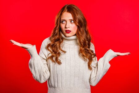 Young unsure girl shrugs her arms, makes gesture of I dont know, care, cant help anything .Young millenial woman on red background