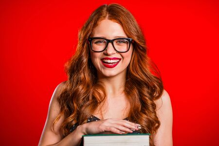 European student on red background in studio holds stack of university books from library. Woman smiles, she is happy to graduate. Stock Photo