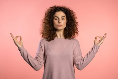 Positive girl relaxing, meditating. Woman calms down, breathes deeply with mudra om on pink studio background. Young curly woman with trendy glitter freckles make-up
