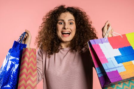 Happy young woman with curly hair and paper bags after shopping isolated on pink studio background. Seasonal sale, purchases, spending money on gifts concept