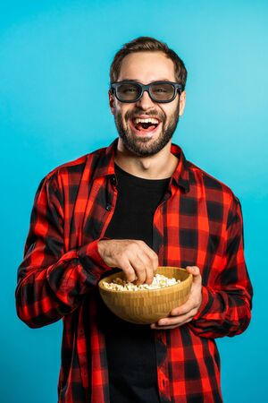 Young european manl in 3d glasses watching fascinating comedy movie, laughing and eating popcorn on blue studio background.