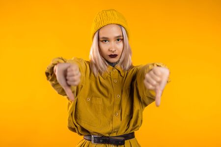 Young pretty woman standing on yellow studio background expressing discontent and showing thumb down gesture at camera. Portrait of girl with sign of dislike 版權商用圖片
