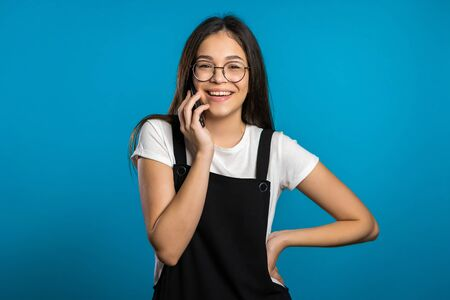 Pretty asian girl with long hair speaks on phone and laughs infectiously from interlocutors jokes. Trendy outfit. Blue studio background