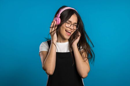 Pretty young asian girl with long hair having fun, smiling, dancing with headphones in studio against blue background. Music, dance, radio concept,