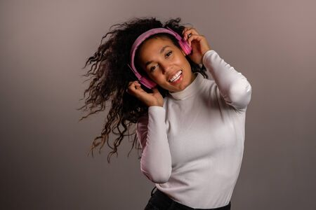 Pretty mixed race girl with curly afro hair having fun, smiling, dancing with headphones in studio on grey background. Music, dance, radio concept.