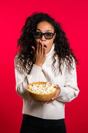 Young african woman in 3d glasses watching horror movie and eating popcorn