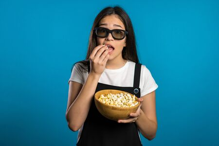 Young asian woman in 3d glasses watching horror movie and eating popcorn on blue studio background. Frightened girl because of unexpectedness plot in film.