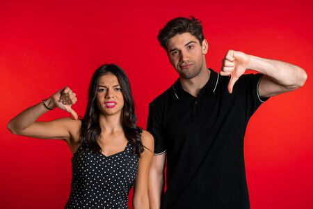 couple on red studio showing thumb down dislike gesture at camera.