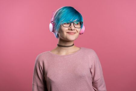 Pretty young girl with blue hair having fun, smiling, dancing with pink headphones in studio on colorful background. Music, dance, radio concept.