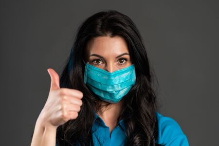 Studio portrait of adult woman in face medical mask, showing thumbs up gesture, isolated on grey background. City air pollution, Covid-19, coronavirus concept.